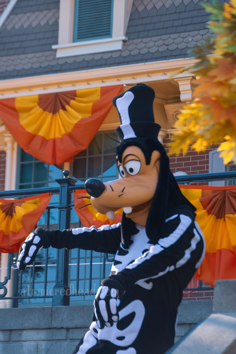 Goofy stands in front of the train station wearing a skeleton costume.