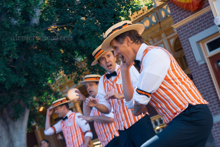 Disneyland's Dapper Days, wearing straw boaters with orange and black band, white collared shirts, black bow ties, and white and orange stripe vests and black pants sing in front of the Fire Station.