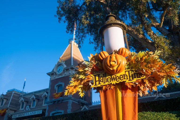 """A sign reading """"Halloween Time"""" is surrounded by orange and yellow leaves, and a Jack O'lantern carved to look like Micky Mouse."""