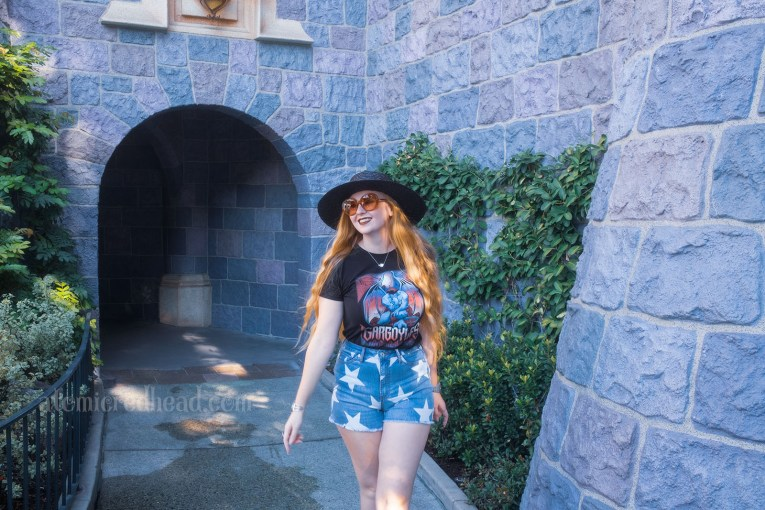 """Myself, wearing a black straw hat, black tee featuring Goliath, a massive gargoyle, and gothic script reading """"Gargoyles"""" below, and jean shorts with white stars on them, standing in front of the stone walls of Sleeping Beauty Castle."""