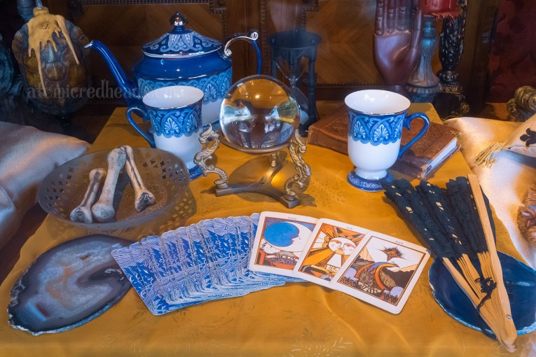 Inside a window of Main Street, a fortune teller appears to have set up shop, a spread of tarot cards sit in front of a crystal ball, and a tea pot sits just past the crystal ball with two tea cups of blue and white.