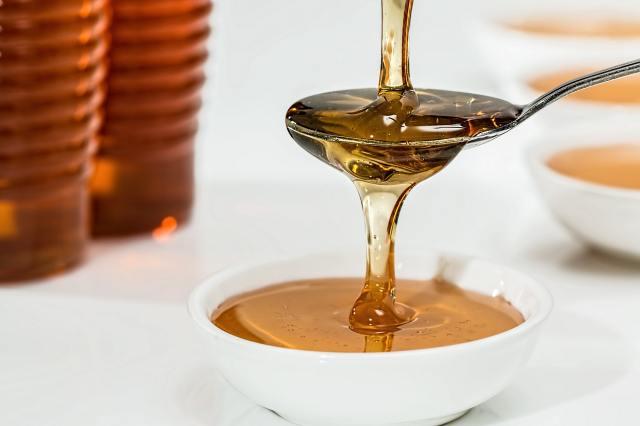 miel liquide qui coule sur une cuillère et un pot
