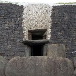The entrance to Newgrange showing the famous carved entrance stone, the doorway, and the roof box above that.