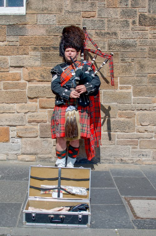 Bagpiper in tartan kilt, black hat, playing his bagpipes on street with a briefcase to collect tips