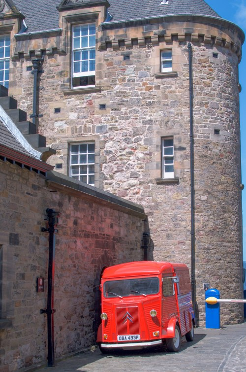 Red bus sitting againt a stone building
