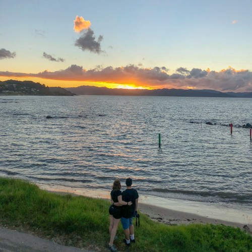 Man and woman embracing, facing away from camera and looking into sunset over calm water