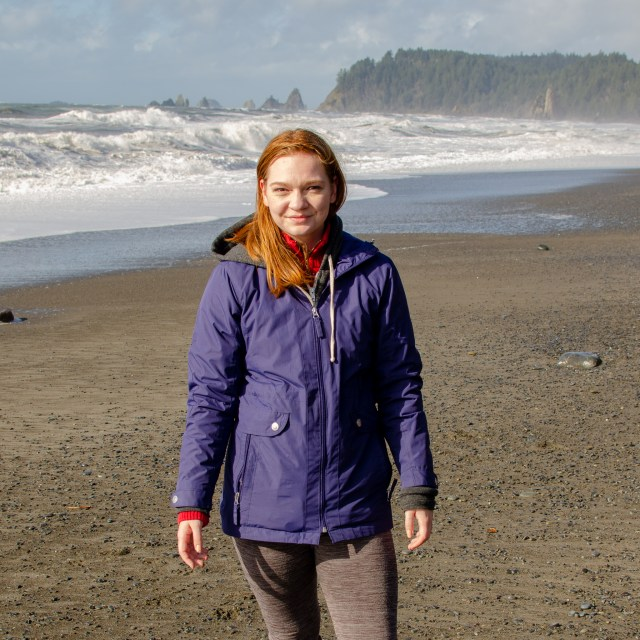 Woman with red hair in purple rain coat standing on beach with big waves crashing in the background