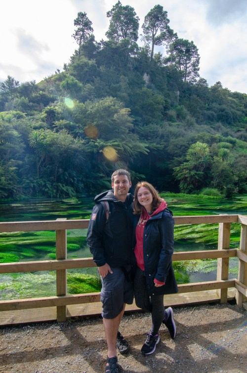 Man and woman standing against a wooden fence, that surrounds the blue and green spring water. There is a thick backdrop of trees and bushes