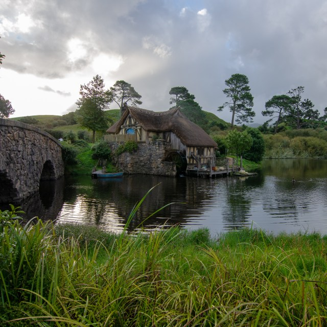 Overlooking a pond, with a stone bridge on the left and a mill in the middle, both set amongst trees and green grass