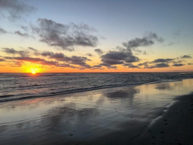 Orange sunset reflecting on beach