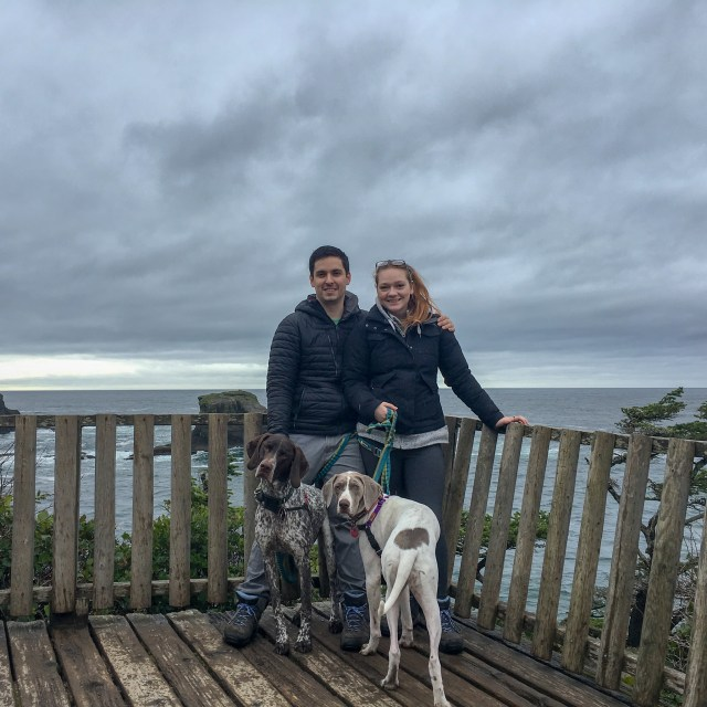 Woman, man, two dogs with cloudy skies and Cape Flattery in the background