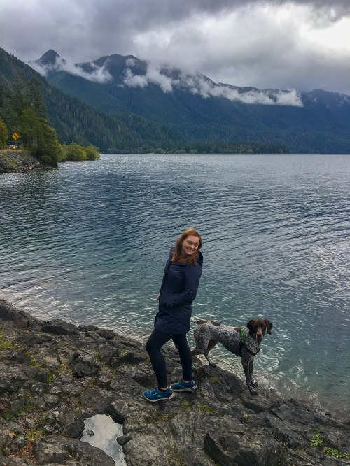Woman and dog at the edge of a blue lake, with cloud covered mountain in the background
