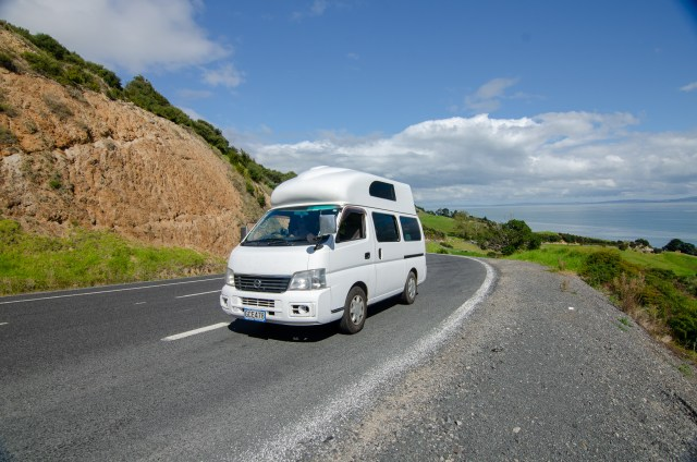 White campervan on the road, with green hills and water in the background