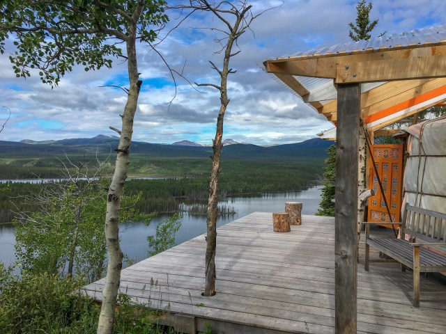 A deck holding a traditional Mongolian yurt, looking out at a lake and forests