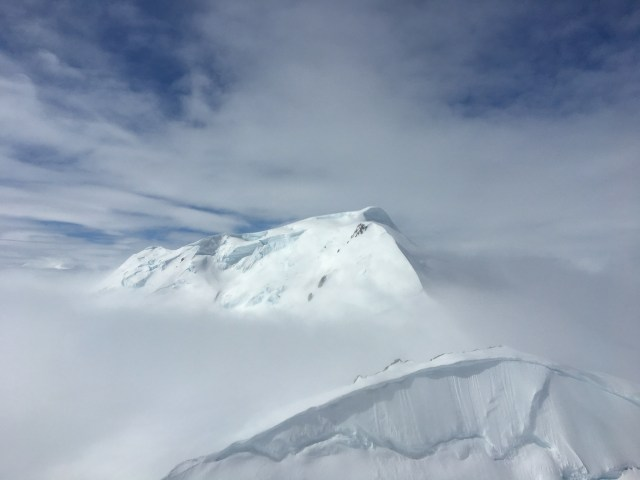 Aerial view of a completely snow covered mountain peak, surrounded by other snow covered mountains