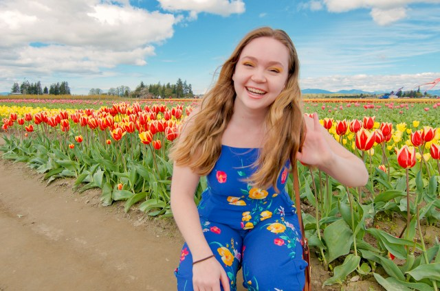 Blonde woman crouching and smiling, with red and yellow tulips behind her