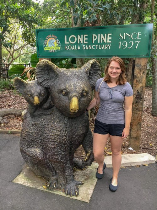Woman smiling beside life-size statue of mom and baby koala, at the entrance to Lone Pine
