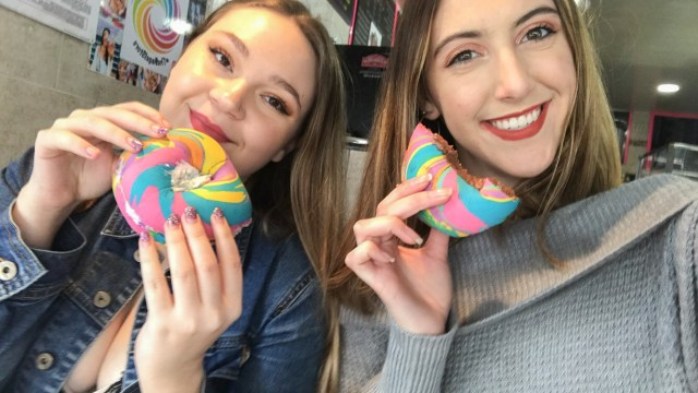 Tow girls, one blonde and one brunette, holding half eaten rainbow bagels