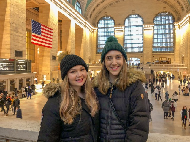 Two girls, one blonde and one brunette, smiling at the camera. Behind them are people walking through Grand Central Station, NYC