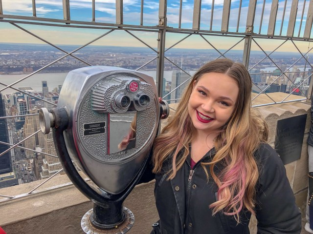 Blonde woman in Winter jacket standing in front of observation binoculars and NYC city skyline