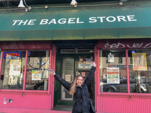 Blonde woman with hands above head, standing in front of The Bagel Store