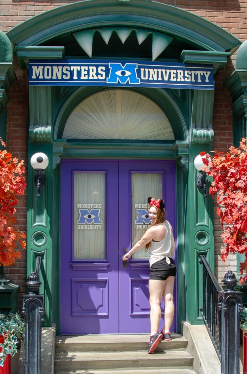Woman in Disney ears facing purple door to Monster's University