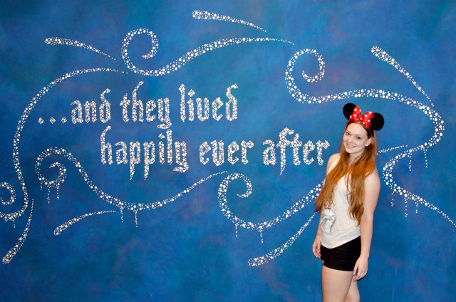 """Woman in red Minnie ears standing in front of blue wall reading """"and they lived happily ever after"""" in silver cursive lettering"""