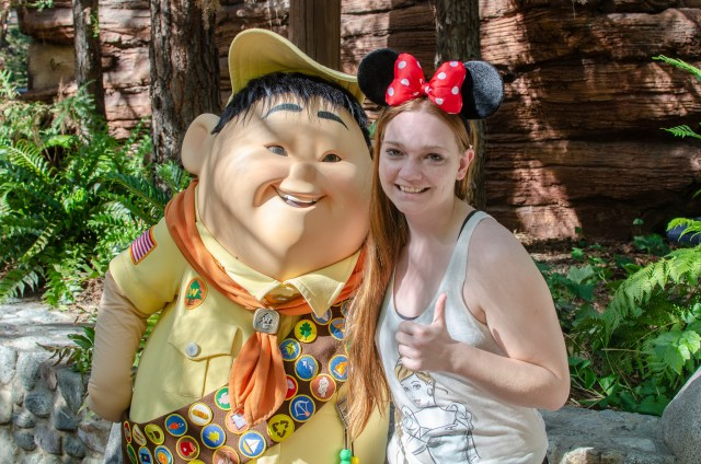 Woman with red Mickey ears meeting costumed character Russell from up at Disneyland