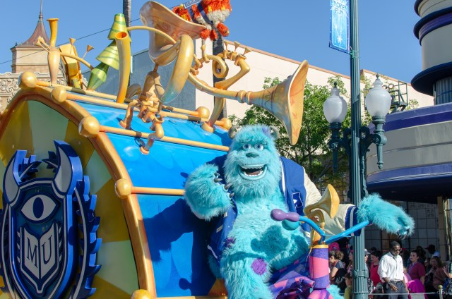 Blue furry monster Sully standing in front of a drum float