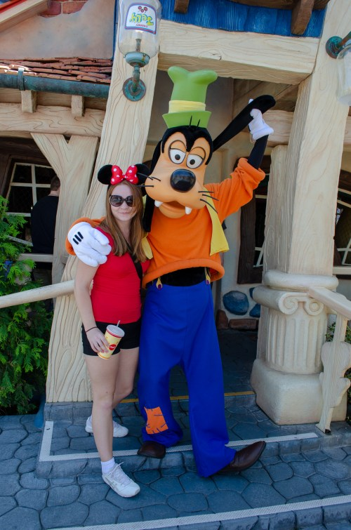 Woman in red and Minnie ears standing beside Goofy in front of a house; he is pulling his ear