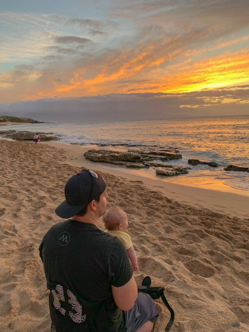 Man with hat backwards holding baby, looking into sunset on the beach