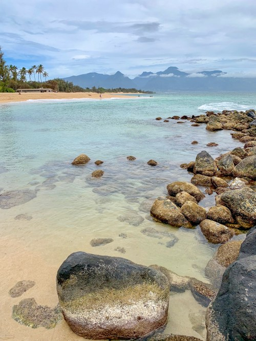 Clear, golden sand beach with mountains in the background