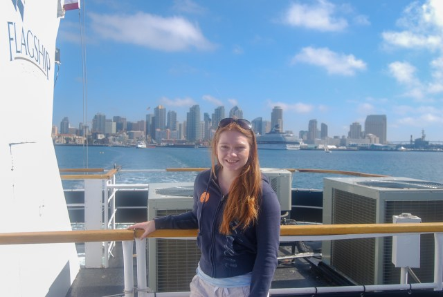 Woman in sweater with sunglasses on, on a boat with a city skyline in the background
