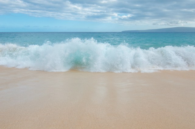 Large white waves crashing on golden sandy beach, with bright blue water in the background