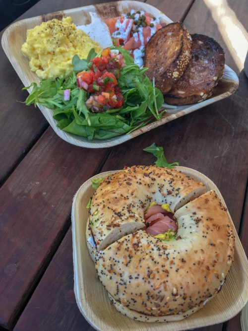 Scrambled eggs, toast & salad and lox bagel served in compostable plates