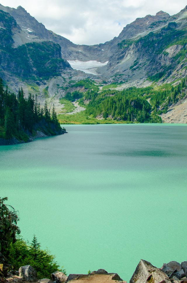 Travelers who love outdoor adventure will love seeing glacial lakes like this green-blue one, surrounded by mountains and a small glacier