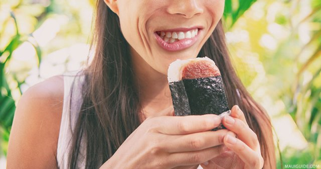Woman eating spam musubi, a local dish that you must try on a visit to Hawaii