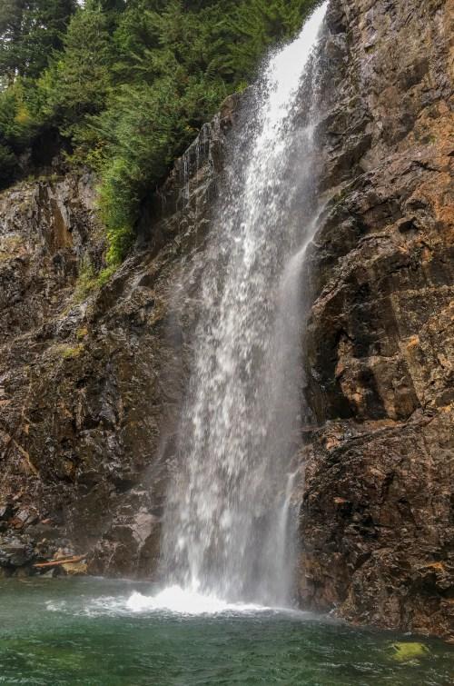 Waterfall falling down rock face into deep green pool