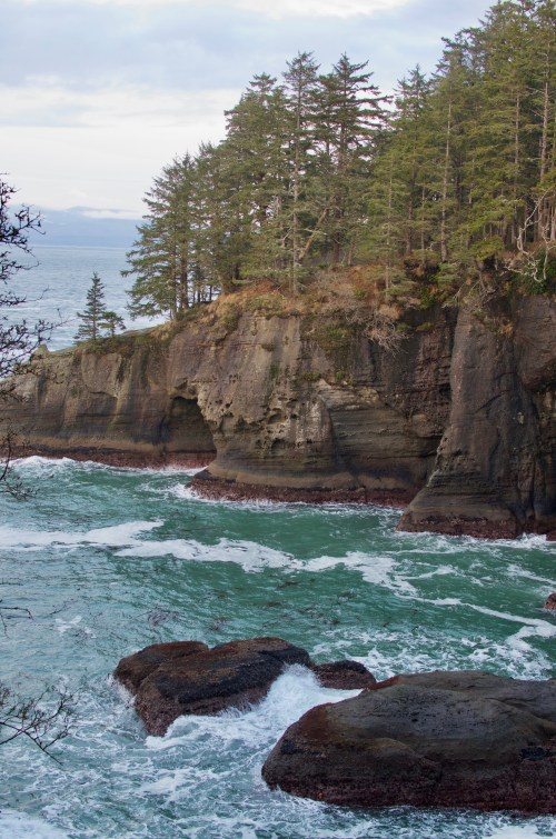 Crumbling rock cliffs that drop right into swirling ocean below. The cliffs are covered in evergreen trees