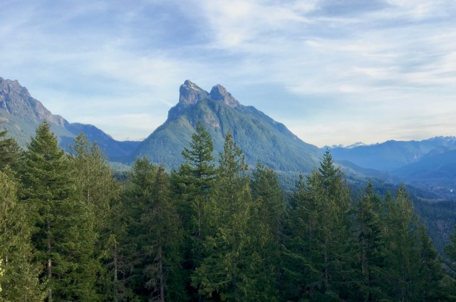 Jagged mountain peak in the distance, evergreen trees in the foreground