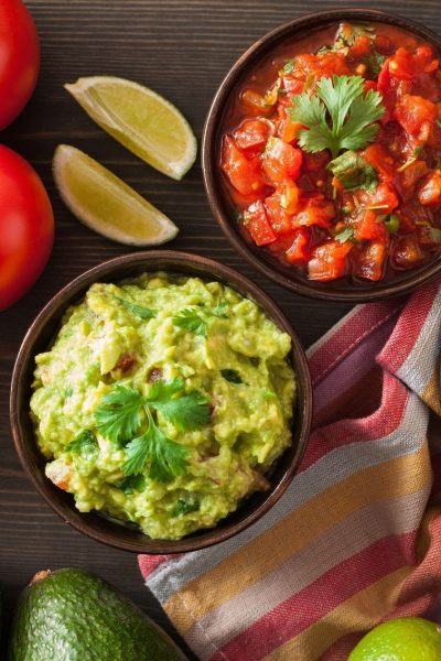 bowl of salsa and bowl of guacamole with limes