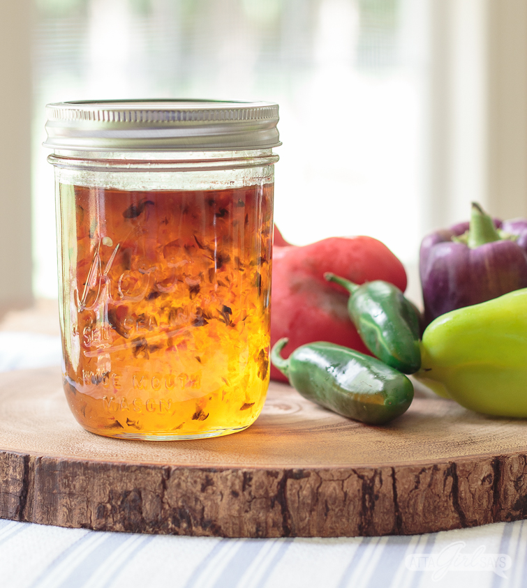 jar of homemade pepper jelly on a wooden slice with a cluster of colorful peppers