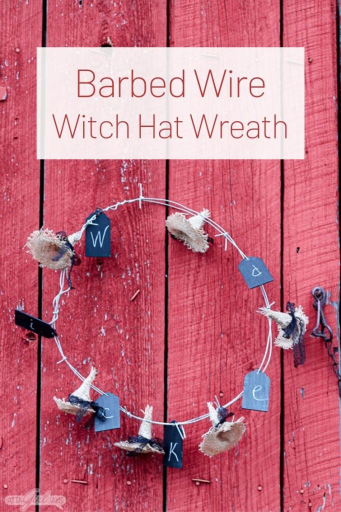Barbed wire wreath with burlap witch hats hanging on a red barn