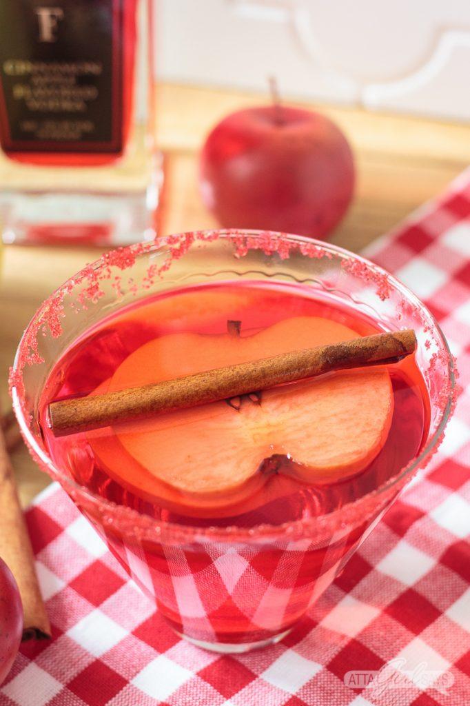 red cinnamon apple martini with an apple slice and cinnamon stick garnish