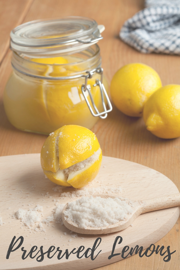 preserved lemon on a cutting board with a wooden spoon filled with salt with a jar of lemons in the background