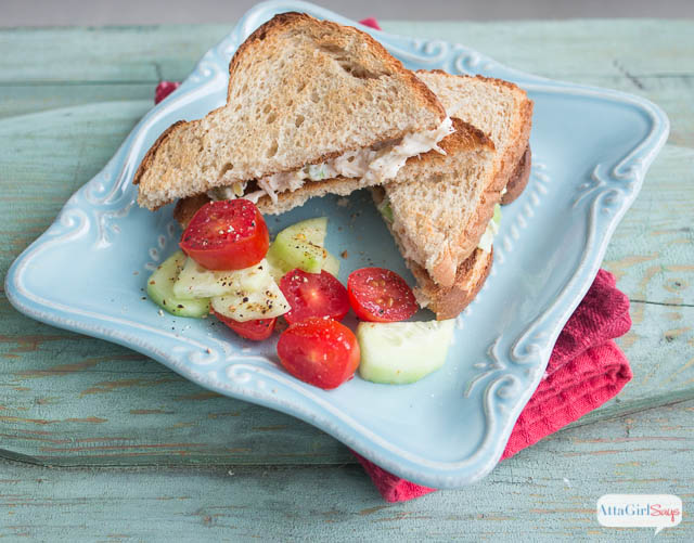 toasted homemade chicken salad sandwich with tomatoes and cucumbers on a plate