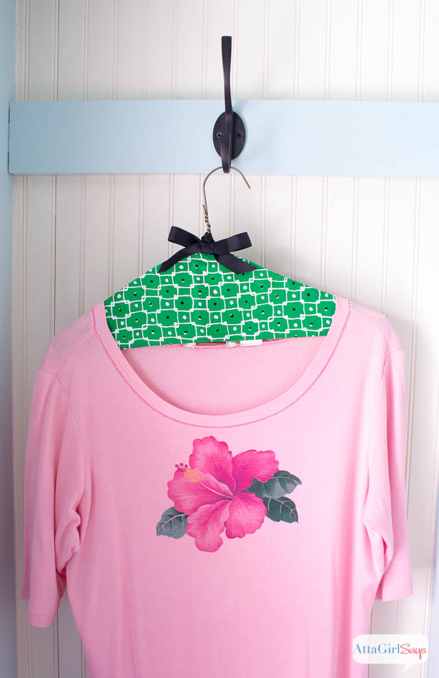 pink hibiscus shirt on a green fabric clothes hanger