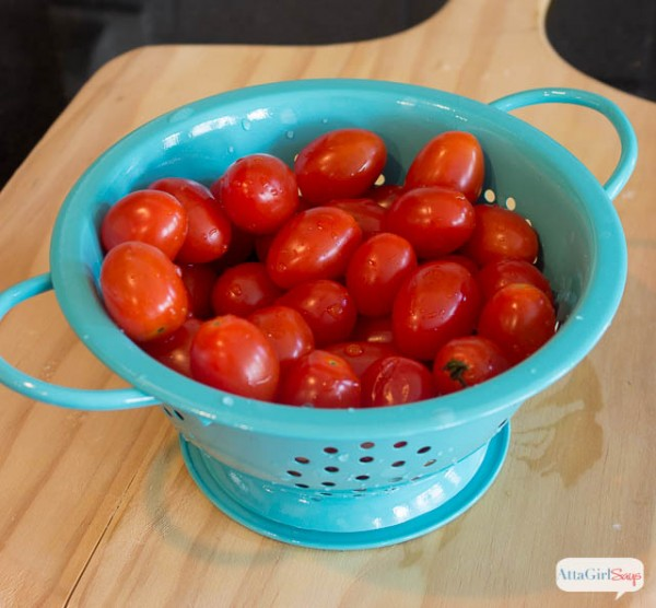 blue colander filled with grape tomatoes