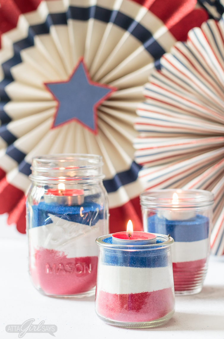 Looking for a easy patriotic decorating ideas for July 4th? Create an easy sand art centerpiece using mason jars, colorful sand and tealight candles. Kids will love helping with this project. Don't miss the video that shows you how to make them! #july4th #patriotic #sandart #redwhiteandblue #kidscrafts