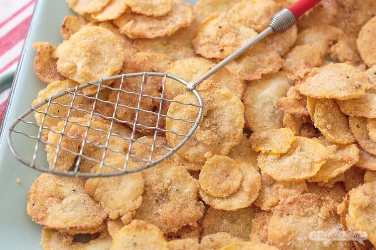metal spider strainer and fried squash chips on a blue enamel platter